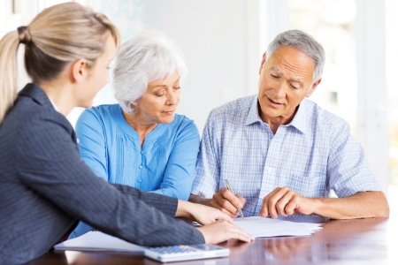 Financial Advisor Explaining Investment Plans To Senior Couple.